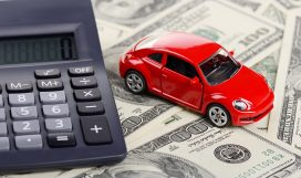 Car toy and calculator stay on the dollars (Installation on the theme of car purchasing and auto credit)