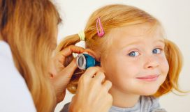 This is a photograph of Pediatrician doctor examining little girl`s ears.