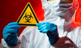 health, medicine and pandemic concept - female doctor holding boihazard caution sign.