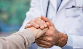 Close up of doctor hand reassuring her female patient at hospital. Closeup hands of medical doctor carefully holding patient's hands. Kind doctor giving real support for patient.
