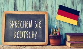 47553327 - a chalkboard with the question sprechen sie deutsch? do you speak german? written in german, a pot with pencils, some books and the flag of germany, on a wooden desk