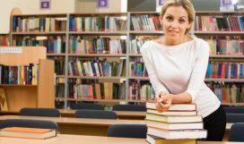 Image of teacher standing near table with books on it in the library