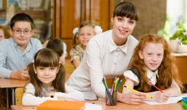 Portrait of diligent schoolgirl at lesson surrounded by her clas