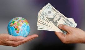 BERLIN, GERMANY - JULY 02: One hand holding a globe, another hand holding dollar bills on July 02, 2014, in Berlin, Germany. (Photo by Thomas Trutschel/Photothek via Getty Images)